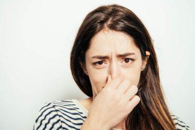 donna che si tappa il naso a causa di un cattivo odore